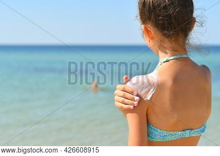 Girl On The Beach Smears Sunscreen On Her Shoulder And Looks At The Sea. Selective Focus On The Shou