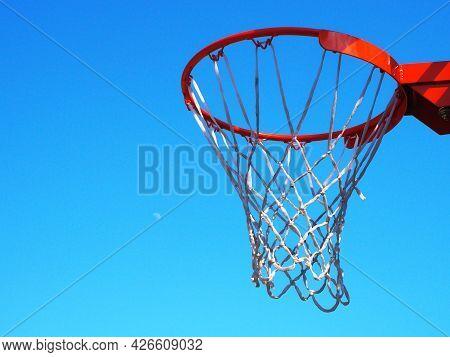Basketball Hoop Against A Cloudless Blue Sky Under The Suns Rays. Closeup Photo