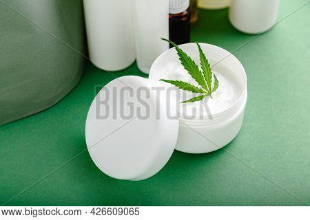 Hemp Moisturizing Cream In White Jar With Cbd Oil Cannabis Leaf And Set Skin Care Cosmetics On Green
