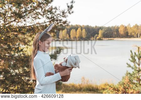 Happy Little Girl In White Polo Shirt With Rabbit Ears Holds Teddy Bear Standing On Riverbank In Sun