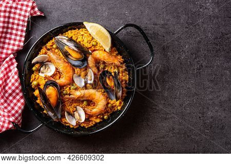Traditional Spanish Seafood Paella On Black Background. Top View. Copy Space