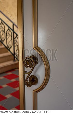 Elegant Open White Door With Golden Decor And Vintage Metal Knob In Spacious Light Hall Of Old Theat