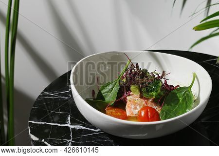 Salmon Steak With Spinach On Whute Plate And Marble Table Closeup