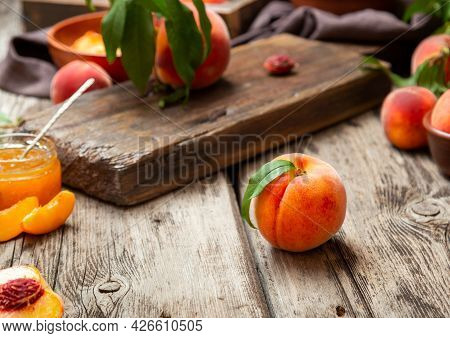 Still Life Peaches On Wooden Table With Cutting Board Knife In Dark Key. Juicy Ripe Peaches On Dark