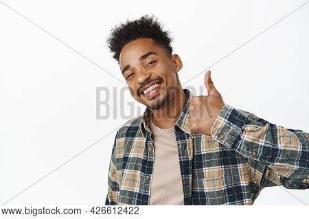 Portrait Of Pleased African American Man Smiling Satisfied, Say Yes, Showing Thumb Up In Approval, E