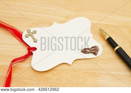 Blank Gift Tag With Red Ribbon Praying Hands, Cross And Pen On Wood Desk With Copy Space For Your Re