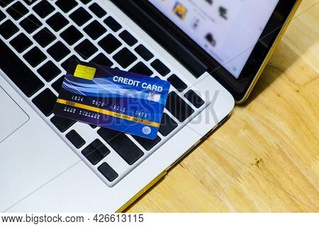 Blue Credit Card Mockup Put On Keyboard Of Laptop And Blurred Web Shopping Online On Display Monitor