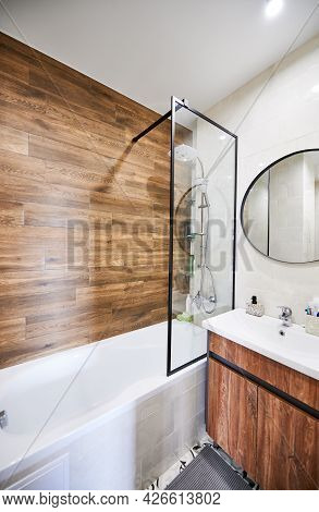 Interior Spacious Bathroom With Modern Furniture In White And Woody Colors And Sink And Round Mirror