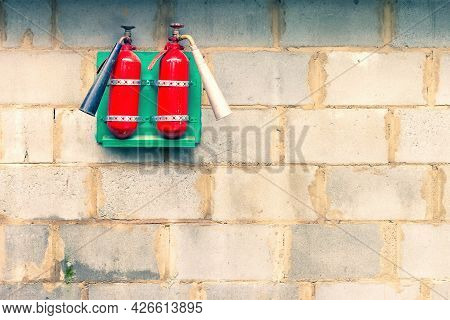 Close Up Of Two Red Fire Extinguishers Hanging On A Panel On A Wall Of Concrete Blocks. The Concept