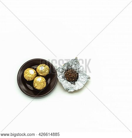 Three Chocolates Are Wrapped In Golden Foil And Lie On A Brown Saucer. Nearby Is One Unrolled Candy.