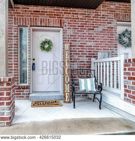 Square Front Of Apartment Building With White Front Door And Red Brick Exterior Wall