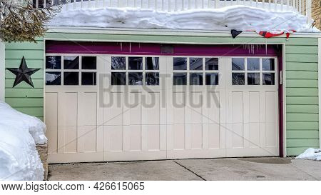 Pano Two Car Garage With Glass Panes On White Door Under Snowed In Balcony Of Home