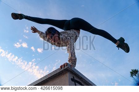 Silhouette Of Flexible Woman Doing Handstand On The Dramatic Sunset And Cityscape.concept Of Desire,