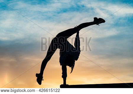 Silhouette Of Female Flexible Acrobat Doing Handstand On The Dramatic Sunset. Concept Of Individuali