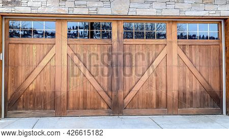 Pano Wide Brown Wood Door With Glass Panes Of Attached Garage Of Stone Brick Home