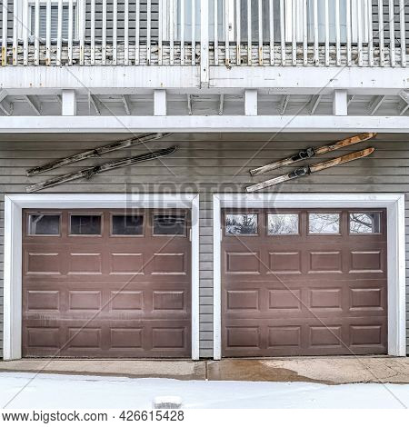 Square Glass Paned Brown Door Of A Two Car Residential Garage On A Snowy Winter Day