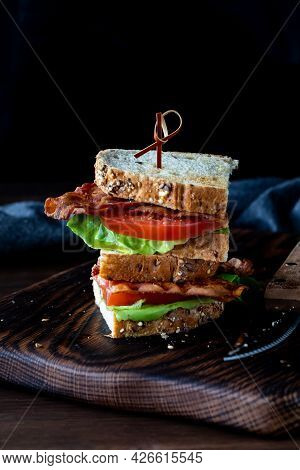 Bacon And Tomato Sandwich Cut In Half And Stacked On Top Of Each Other, On A Wooden Board.