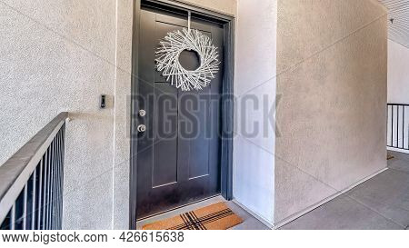 Pano Apartment Unit With White Wreath Dark Gray Door And Doormat At The Entrance