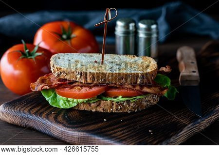 Front Facing View Of A Toasted Bacon And Tomato Sandwich With Salt And Pepper Shakers In Behind And