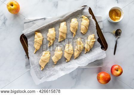 Top Down View Of Crescent Rolls With Apple Filling On A Parchment Lined Baking Sheet, Ready For Baki