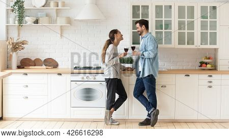 Couple Chatting While Standing In Cozy Modern Kitchen With Wineglasses