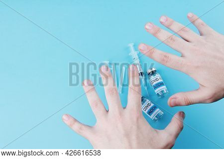 The Hands Of A Young Man, Vials Of Vaccine And Syringes On A Blue Medical Background. The Concept Of