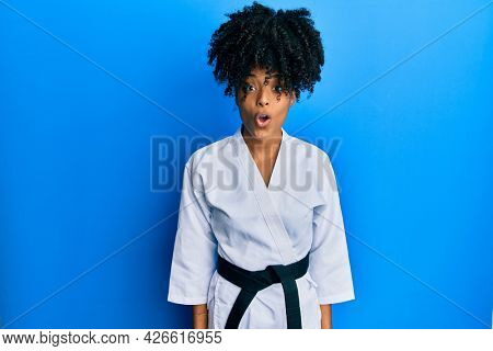 African american woman with afro hair wearing karate kimono and black belt afraid and shocked with surprise expression, fear and excited face.