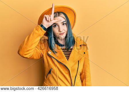 Young modern girl wearing yellow hat and leather jacket making fun of people with fingers on forehead doing loser gesture mocking and insulting.