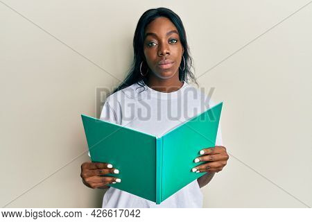 Young african american woman reading book relaxed with serious expression on face. simple and natural looking at the camera.