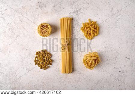 Uncooked Raw Bunch Of Spaghetti, Fettuccine, Girandole And Tagliatelle On Grey Textured Background.
