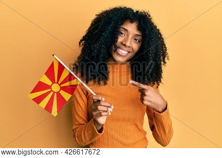 African american woman with afro hair holding macedonia flag smiling happy pointing with hand and finger