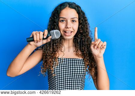 Teenager hispanic girl singing song using microphone smiling with an idea or question pointing finger with happy face, number one