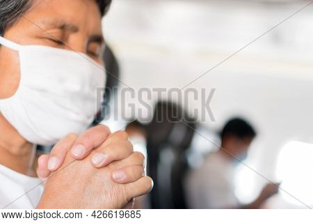 Elderly Asian Female Passenger Wearing Face Mask, Closed His Eyes, Praying To God While On Board The