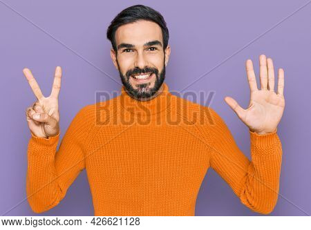 Young hispanic man wearing casual clothes showing and pointing up with fingers number seven while smiling confident and happy.
