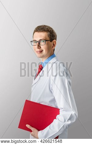 Portrait Of A Young Smiling Successful Doctor Caucasian Man In Uniform On A White Isolated Backgroun