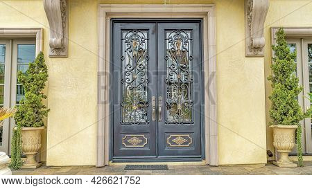 Pano Double Door With Decorative Wrought Iron And Glass Panes At The House Entrance