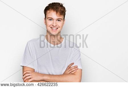 Young caucasian man wearing casual white t shirt happy face smiling with crossed arms looking at the camera. positive person.