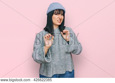 Young hispanic woman wearing cute wool cap disgusted expression, displeased and fearful doing disgust face because aversion reaction. with hands raised