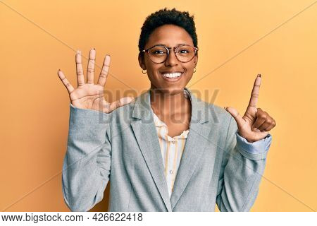 Young african american girl wearing business jacket and glasses showing and pointing up with fingers number seven while smiling confident and happy.