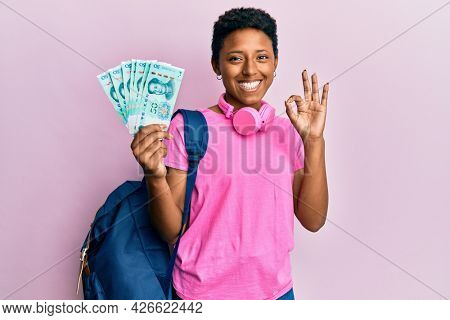 Young african american girl wearing student backpack holding chinese yuan banknotes doing ok sign with fingers, smiling friendly gesturing excellent symbol