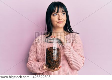 Young hispanic woman holding jar of raisins smiling looking to the side and staring away thinking.