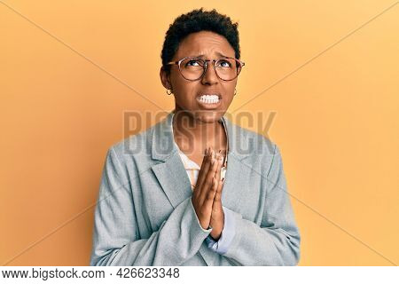 Young african american girl wearing business jacket and glasses begging and praying with hands together with hope expression on face very emotional and worried. begging.