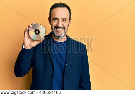 Middle age hispanic man holding compact disc looking positive and happy standing and smiling with a confident smile showing teeth