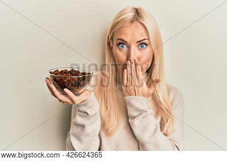 Young blonde woman holding bowl with raisins covering mouth with hand, shocked and afraid for mistake. surprised expression