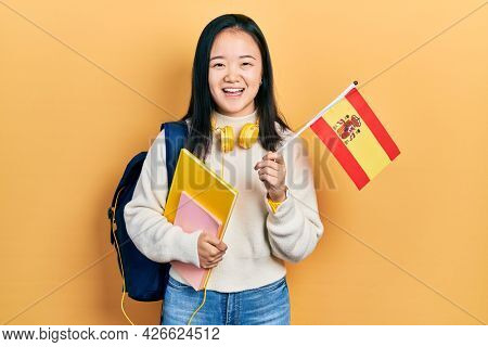 Young chinese girl exchange student holding spanish flag smiling and laughing hard out loud because funny crazy joke.