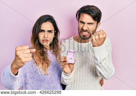 Beautiful couple of boyfriend and girlfriend holding engagement ring for proposal annoyed and frustrated shouting with anger, yelling crazy with anger and hand raised
