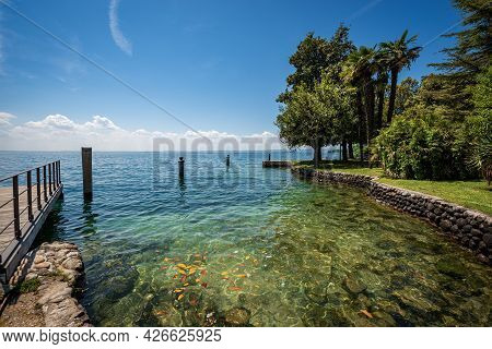 Beautiful Coastline In Front Of The Small Town Of Garda, Tourist Resort On The Coast Of Lake Garda (
