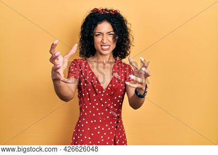 Young latin girl wearing summer dress shouting frustrated with rage, hands trying to strangle, yelling mad