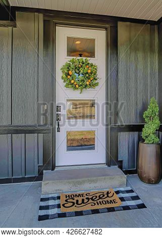 Vertical Lovely Home Entrance With Wreath And Potted Plant By The Glass Paned Front Door