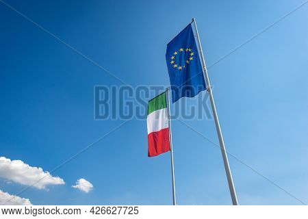 Italian And European Union Flags With Flagpole, Blowing In The Wind On A Clear Blue Sky With Clouds